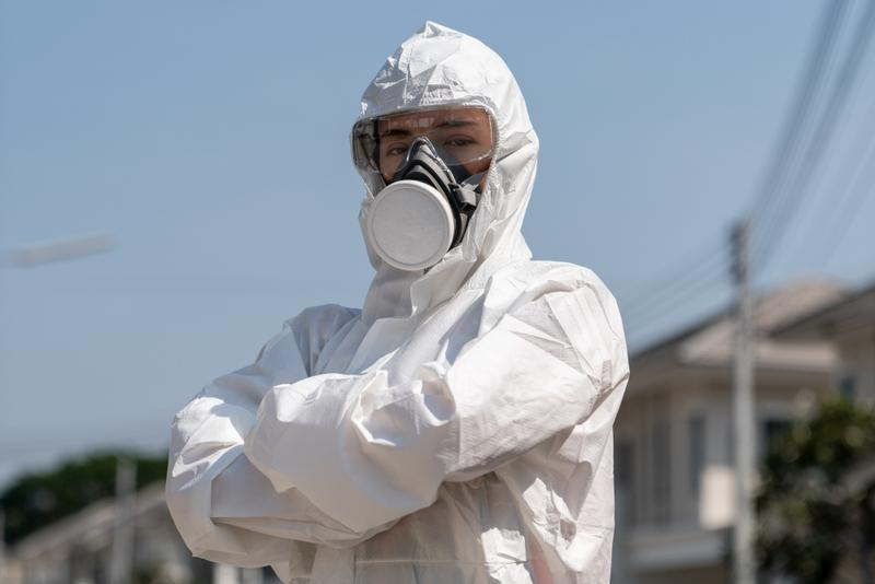 Woman wearing gloves with biohazard chemical protective suit and